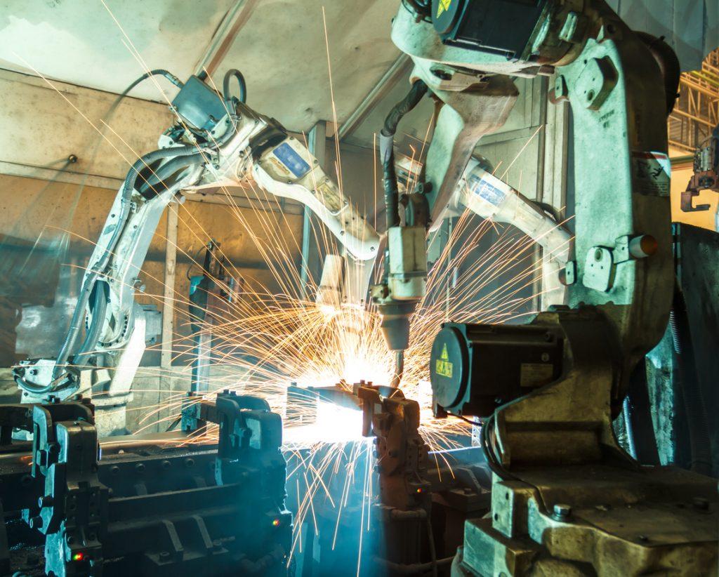 Team of welding robots welding a machine together