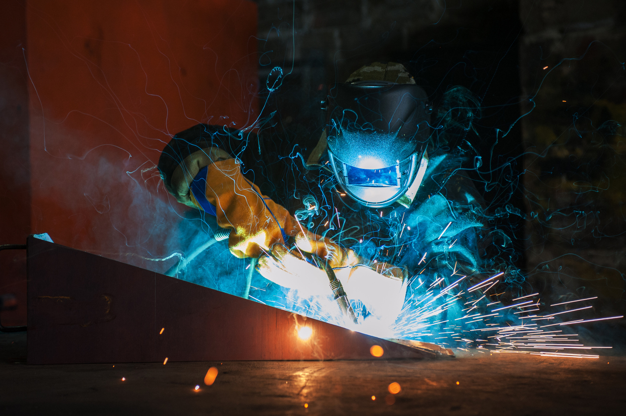 Working welding metal at a factory